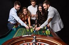 a roulette wheel with people standing around betting