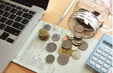 photo of laptop, bank statement, calculator and coins spilling out of a jar all indicating online money management