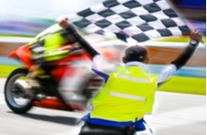 motorcycle race with a checkered flag waving in the winner