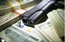 pile of money with gun and bullets