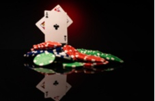 pile of poker chips with a Jack and an Ace card sticking out at the tops of the pile
