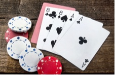 poker hand showing two aces and two eights with poker chips scattered around
