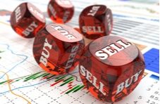 red dice with Buy and Sell written on them sitting on a stock market graph